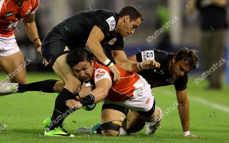 Sunwolves Shunsuke Nunomaki, center, is tackled by Jaguares' Joaquin Tuculet, left, and Juan Martin Hernandez, during a Super Rugby match in Buenos Aires, Argentina