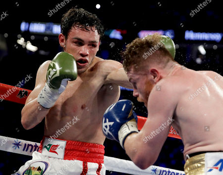 Canelo Alvarez, right, of Mexico, gets hit by Julio Cesar Chavez Jr., of Mexico, during their catch weight boxing match, in Las Vegas