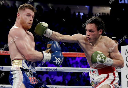 Canelo Alvarez, left, of Mexico, fights Julio Cesar Chavez Jr., of Mexico, during their catch weight boxing match, in Las Vegas
