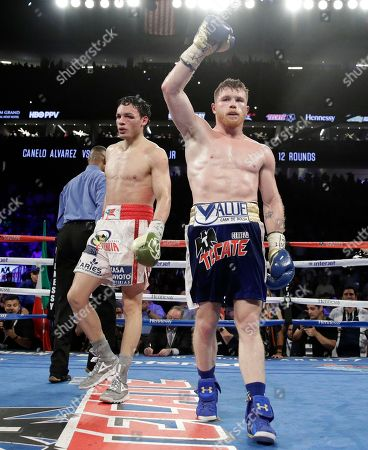Canelo Alvarez, of Mexico, right, celebrates after defeating Julio Cesar Chavez Jr., of Mexico, in a catch weight boxing match, in Las Vegas
