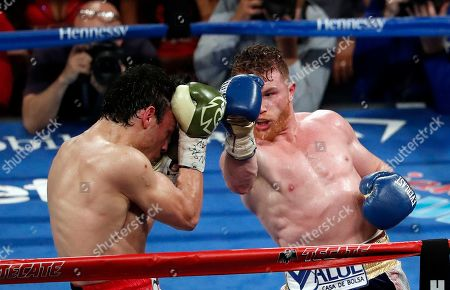 Canelo Alvarez, of Mexico, right, punches Julio Cesar Chavez Jr., of Mexico, during their catch weight boxing match, in Las Vegas