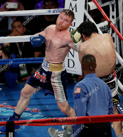 Canelo Alvarez, of Mexico, left, punches Julio Cesar Chavez Jr., of Mexico, during their catch weight boxing match, in Las Vegas