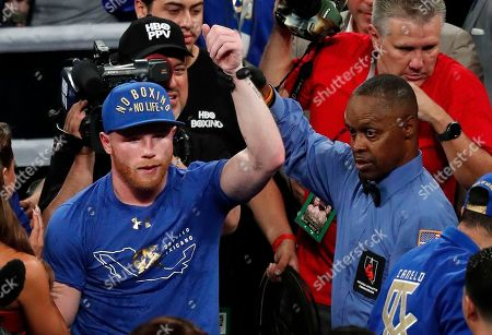Referee Kenny Bayless, right, raises the arm of Canelo Alvarez, of Mexico, after Alvarez defeated Julio Cesar Chavez Jr., of Mexico, in a catch weight boxing match, in Las Vegas