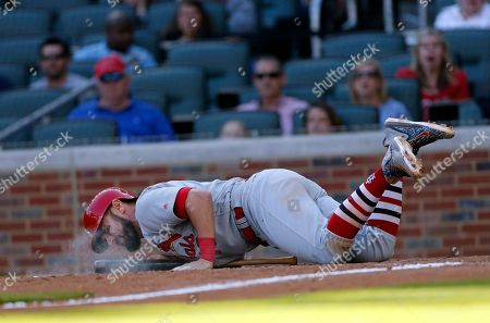 Stock Photo of St. Louis Cardinals' Matt Carpenter (13) falls after fouling a ball off his foot in the 13th inning of a baseball game against the Atlanta Braves, in Atlanta. The Cardinals won 6-4 in14 innings