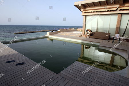 Stock Image of A View of the Swimming Pool of the Ransacked Summer House of Hannibal Gaddafi Son of Muammar Gaddafi at the Select Regata Beach Resort in Tripoli on 01 September 2011 Algeria's Foreign Ministry Had Confirmed on 30 August 2011 That Gaddafi's Wife Safia and Three of His Eight Children the Daughter and Two Sons Hannibal and Mohamed Had Crossed the Libyan-algerian Border Meanwhile the Fugitive Libyan Leader Muammar Gaddafi is 'Hiding' in a Desert Town Outside Tripoli Planning a Fightback a Senior Rebel Commander Said 01 September the Exact Whereabouts of Gaddafi Remained Unknown on 01 September Marking the 42nd Anniversary of His Seizing Power in the Northern African Country in a Military Coup Libyan Arab Jamahiriya Tripoli