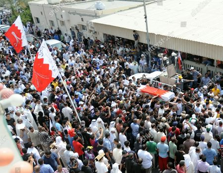 Mourners Carry the Coffin of Killed 14-year-old Bahraini Ali Jawad Al-sheikh (right) During His Funeral Procession in Sitra Village South-west of the Bahraini Capital Manama on 01 September in a Procession That was Attended by Thousands Al-sheikh Had Died a Day Earlier on 31 August 2011 the First Day of Marking Eid El-fitr For Many Shiites in Bahrain by Anti-riot Police As They Chased Him Down According to Family and Fellow Protesters Bahraini Police Denied Being Involved in the Incident Sighting That No Clashes Were Taking Place in the Area at the Time the Police Also Said That They Were Investigating the Incident Bahrain Sitra