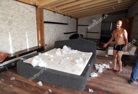 Stock Photo of An Unidentified Libyan Man Points at the Ransacked Bed at the Seaside Summer House of Hannibal Gaddafi Son of Muammar Gaddafi at the Select Regata Beach Resort in Tripoli on 01 September 2011 Algeria's Foreign Ministry Had Confirmed on 30 August 2011 That Gaddafi's Wife Safia and Three of His Eight Children the Daughter and Two Sons Hannibal and Mohamed Had Crossed the Libyan-algerian Border Meanwhile the Fugitive Libyan Leader Muammar Gaddafi is 'Hiding' in a Desert Town Outside Tripoli Planning a Fightback a Senior Rebel Commander Said 01 September the Exact Whereabouts of Gaddafi Remained Unknown on 01 September Marking the 42nd Anniversary of His Seizing Power in the Northern African Country in a Military Coup Libyan Arab Jamahiriya Tripoli