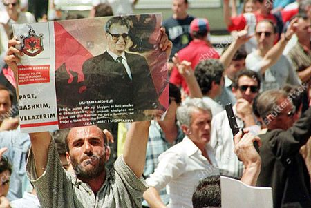A Supporter of Albanian Would-be King Leka i Holds Up a Portrait of Him As Another Man Shows a Gun During a Monrachist Demo in the Centre of Tirana 03 July Following the Rally Bursts of Gunfire Broke out and Several Loud Explosions Echoed Off Building and Surrounding Hills One Person Reportedly was Killed in the Shootings Albania Tirana