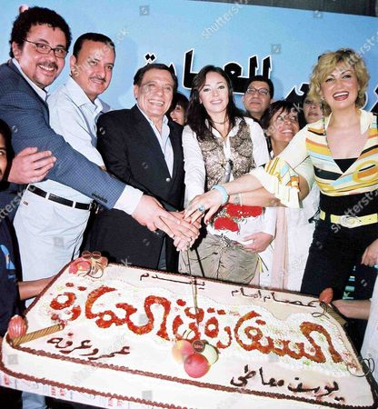 Famous Egyptian Artist Adel Emam Cuts the Cake Accompanied by the Cast For the New Film 'Alsafara Fe Alemara' in Cairo Sunday 08 May 2005