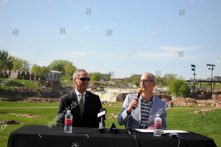 Gov. Dennis Daugaard, left, and Tourism Secretary Jim Hagen, right, hold a tourism event in Sioux Falls, S.D., . Officials say they're hopeful for a strong summer tourism season even without major anniversaries that have been a big draw for visitors in recent years