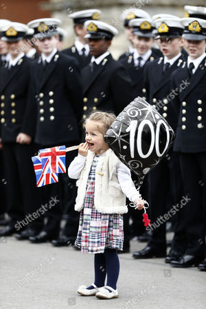 Young Esme Sutton, daughter of a staff member, plays with a balloon and a national flag as she awaits the arrival of Queen Elizabeth II and Prince Philip to Pangbourne College on the occasion of the school's centenary