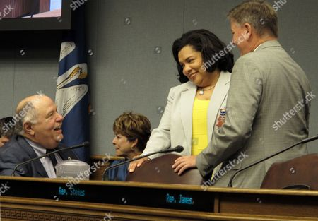 Revenue Secretary Kimberly Robinson, center, talks with state Reps. Jim Morris, R-Oil City, left, and Chris Broadwater, R-Hammond, right, ahead of a House Ways and Means Committee hearing on tax proposals, in Baton Rouge, La