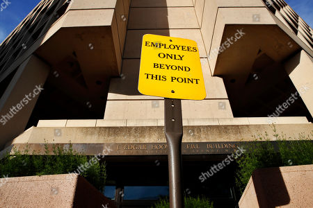 "A sign announces ""Employees Only Beyond This Point"" at an entrance to the J. Edgar Hoover FBI building in Washington, . President Donald Trump abruptly fired FBI Director James Comey Tuesday, ousting the nation's top law enforcement official in the midst of an investigation into whether Trump's campaign had ties to Russia's election meddling"