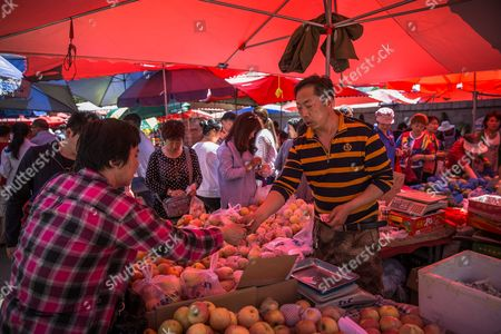 A vendor sells fruits and vegetables to Chinese customers in a market in Beijing, China, 10 May 2017. China's consumer price index (CPI), a main gauge of inflation, in April rose 1.2 percent on year after gaining 0.9 percent in March. The producer price index (PPI) in April rose 6.4 percent from a year earlier, according to figures released by the National Bureau of Statistics on 10 May.