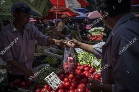 A Chinese customer (R) buys tomatoes in a market in Beijing, China, 10 May 2017. China's consumer price index (CPI), a main gauge of inflation, in April rose 1.2 percent on year after gaining 0.9 percent in March. The producer price index (PPI) in April rose 6.4 percent from a year earlier, according to figures released by the National Bureau of Statistics on 10 May.