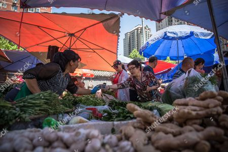 A Chinese customer gives money to a vendor as she buys vegetables in a market in Beijing, China, 10 May 2017. China's consumer price index (CPI), a main gauge of inflation, in April rose 1.2 percent on year after gaining 0.9 percent in March. The producer price index (PPI) in April rose 6.4 percent from a year earlier, according to figures released by the National Bureau of Statistics on 10 May.