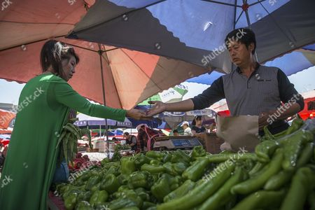 A Chinese customer receives change from a vendor as she buys vegetables in a market in Beijing, China, 10 May 2017. China's consumer price index (CPI), a main gauge of inflation, in April rose 1.2 percent on year after gaining 0.9 percent in March. The producer price index (PPI) in April rose 6.4 percent from a year earlier, according to figures released by the National Bureau of Statistics on 10 May.
