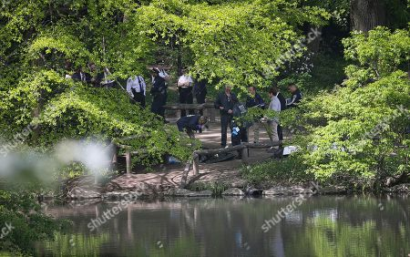 Medical examiner officials, center, take photos of a body pulled from a pond in Central Park, in New York. The discovery came a day after the body of another man was recovered in the Jacqueline Kennedy Onassis Reservoir in the park. New York City police say the deaths of two men found in Central Park lakes don't appear to be crime-related