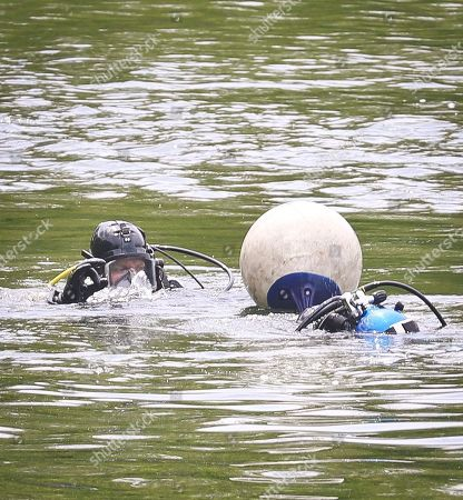 NYPD divers exchange hand signals near a floating marker, as search efforts continue at the Jacqueline Kennedy Onassis Reservoir near Central Park West and 90th Street a day after a man's body was recovered there, in New York