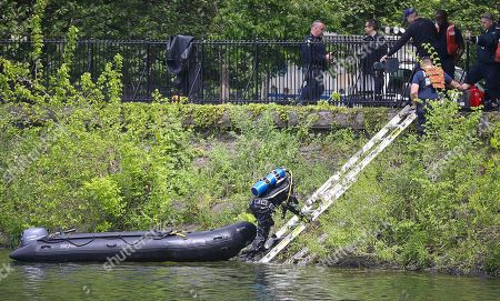 An NYPD diver climbs from the Jacqueline Kennedy Onassis Reservoir near Central Park West and 90th Street, as search efforts continue a day after a man's body was recovered there, in New York