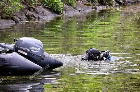 A NYPD diver searches the Jacqueline Kennedy Onassis Reservoir near Central Park West and 90th Street, in New York. The bodies of two men have been discovered over two days in Central Park, each floating in a lake, but investigators don't believe either was the victim of a crime, police said