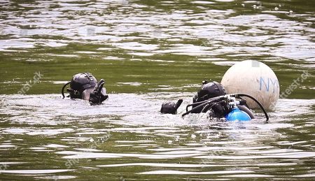 NYPD divers exchange hand signals near a floating marker as search efforts continue at the Jacqueline Kennedy Onassis Reservoir near Central Park West and 90th Street, in New York. The bodies of two men have been discovered over two days in Central Park, each floating in a lake, but investigators don't believe either was the victim of a crime, police said