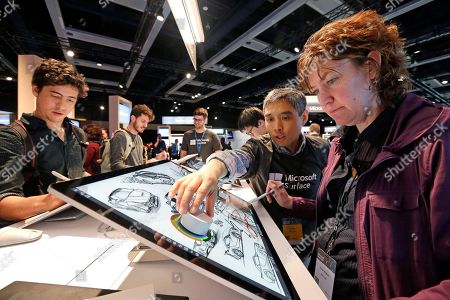 Microsoft employee Anne Walker, right, is shown a Surface Studio device by Fei Su at the Microsoft Build 2017 developers conference, in Seattle. Earlier in the day at the annual event, Microsoft CEO Satya Nadella said that a half billion devices are now running Windows 10, its latest operating system. That's up from 400 million disclosed last September, but far short of a goal of 1 billion by 2018