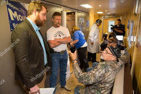 IMAGE DISTRIBUTED FOR ASPEN DENTAL - Local volunteers from Aspen Dental provide veterans with free dental care, in Dayton, Ohio on the MouthMobile, a fully equipped dental office on wheels. This community-giving event is part of Aspen Dental's Healthy Mouth Movement, which stops in 35 cities throughout the country to bring much needed care to veterans. Geoff Daniels, regional representative for Senator Sherrod Brown, speaks with AmVets Post 24 Commander Bill Jenks and two veterans