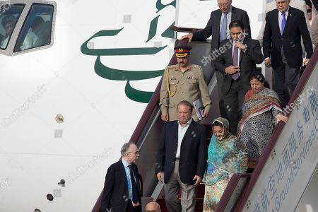 Stock Image of Nawaz Sharif, Kalsoom Nawaz Sharif A pilot looks back as Pakistani Prime Minister Nawaz Sharif, center, and his wife Kalsoom Nawaz Sharif arrive on a flight at Beijing's International Airport ahead of the Belt and Road Forum in Beijing