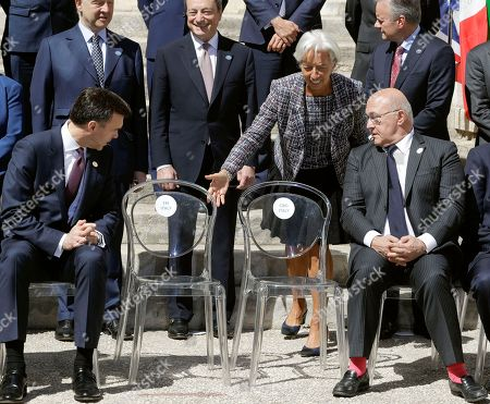 Canadian Finance Minister William Morneau, left, French Finance Minister Michel Sapin, right, and International Monetary Fund Managing Director Christine Lagarde, standing at center right, look at the empty chairs of the Italian delegation as they wait with other participants for their family photo to be taken at the Norman-Swabian Castle, venue of the G7 of finance ministers, in Bari, southern Italy