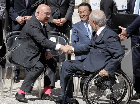 French Finance Minister Michel Sapin, left, shakes hands with German Finance Minister Wolfgang Schaeuble as Japanese Finance Minister Taro Aso looks on before a family photo at the Norman-Swabian Castle, venue of the G7 of finance ministers, in Bari, southern Italy