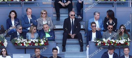 Former tennis player Ilie Nastase, in dark glasses at left, and Real Madrid soccer player Cristiano Ronaldo third right centre row watch the mens semifinal tennis match between Rafael Nadal of Spain and Novak Djokovic of Serbia at the Madrid Open tennis tournament in Madrid, Spain