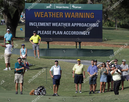 J.B. Holmes J. B. Holmes, right, hits from rough in the 11th hole as a weather warning is posted on the course in the third round of The Players Championship golf tournament, in Ponte Vedra Beach, Fla