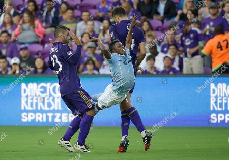 Sporting Kansas City's Latif Blessing, center, gets airborne as he gets caught between Orlando City's Antonio Nocerino (23) and Orlando City's Jose Aja during the first half of an MLS soccer game, in Orlando, Fla