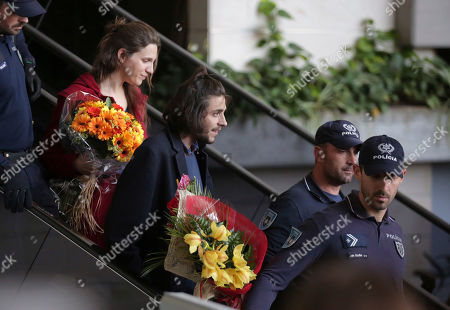 """Salvador Sobral, center, and his sister Luisa Sobral look at cheering fans at Lisbon airport escorted by policemen, after winning the final of the Eurovision Song Contest with his song """"Amar pelos dois"""", in Kiev"""