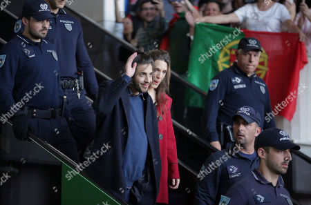 """Salvador Sobral, center, an his sister Luisa Sobral look at cheering fans at Lisbon airport escorted by policemen, after winning the final of the Eurovision Song Contest with his song """"Amar pelos dois"""", in Kiev"""