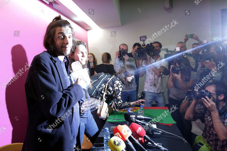 """Salvador Sobral, left, and his sister Luisa Sobral, are lit by a camera flash, as they arrive for a news conference holding the Eurovision award, at the Lisbon airport, after winning the Final of the Eurovision Song Contest with his song """"Amar pelos dois"""", in Kiev, Ukraine, Saturday"""