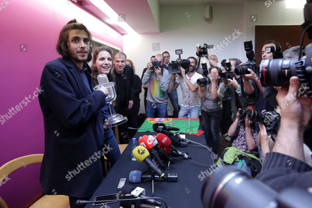 """Salvador Sobral, left, and his sister Luisa Sobral, arrive for a news conference holding the Eurovision award, at Lisbon airport, after winning the final of the Eurovision Song Contest with his song """"Amar pelos dois"""", in Kiev"""