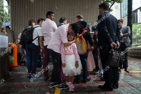 Stock Photo of Rejected asylum seeker Vanessa Mae Bondalian Rodel, 40, (C), hugs her daughter Kellepatha Sanuthi Keana Nihinsa, five, while their lawyer (back) speaks during a press conference outside the Immigration Tower in Hong Kong, China, 15 May 2017. Hong Kong's immigration authority has rejected the cases of the asylum seekers families who sheltered American whistle-blower Edward Snowden in Hong Kong in 2013. Tibbo has 14 days to appeal the decision, which could extend their stay, as they now face an imminent risk of detention and deportation.