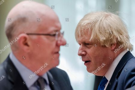 Britain's Foreign Secretary Boris Johnson, right, walks by Ireland's Foreign Minister Charles Flanagan during a meeting of EU foreign ministers at the Europa building in Brussels