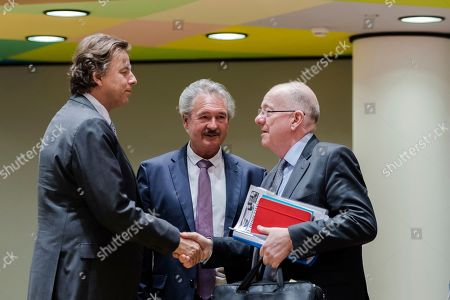 Dutch Foreign Minister Bert Koenders, left, greets Ireland's Foreign Minister Charles Flanagan, right, and Luxembourg's Foreign Minister Jean Asselborn during a meeting of EU foreign ministers at the Europa building in Brussels