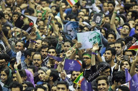 Supporters of Iran's President Hassan Rouhani are holding posters of Mir Hossein Mousavi (an Iranian reformist politician and leader of the Green Movement, from 2009. He is under house arrest with his wife and Mehdi Karroubi) on a campaign rally in Tehran's Azadi Stadium