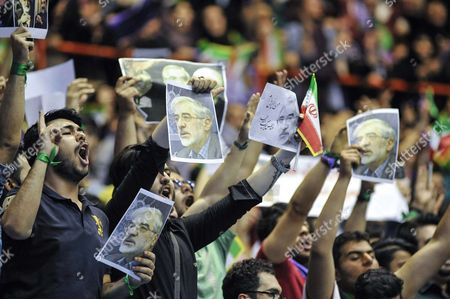 Stock Image of Supporters of Iran's President Hassan Rouhani are holding posters of Mir Hossein Mousavi (an Iranian reformist politician and leader of the Green Movement, from 2009. He is under house arrest with his wife and Mehdi Karroubi) on a campaign rally in Tehran's Azadi Stadium