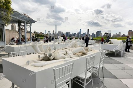 """Visitors view """"The Theater of Disappearance"""" by Adrian Villar Rojas, and the Manhattan skyline in the Roof Garden of the Metropolitan Museum of Art, in New York"""