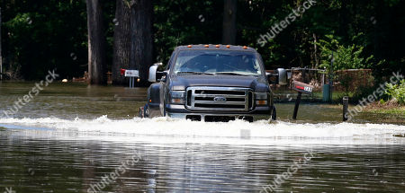 A resident drives his truck from their flooded property along Chickasaw Road in Warren County, near Vicksburg, Miss., . MDOT crews will close a section of State Route 465 from U.S. Highway 61 to the backwater levee in Warren County on Tuesday, based on the Mississippi River's forecasted crest of 48 feet on May 19, at Vicksburg