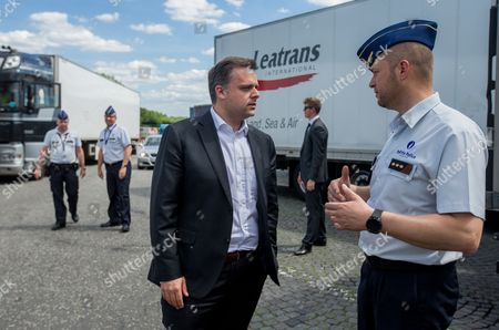 Stock Image of Philippe De Backer, Secretary of State for the Fight against Social Fraud, Protection of Privacy and the North Sea, Deputy Minister for Social Affairs and Public Health (L) chat with a policeman  during a tachograph check  in Brussels, Belgium, 16 May 2017. The Belgian police and experts from Poland, the Netherlands, France, Germany, Denmark and Ireland carry out a checking operation in order to detect the handling of the tachograph used by heavy goods vehicles.