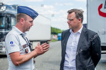 Stock Photo of Philippe De Backer, Secretary of State for the Fight against Social Fraud, Protection of Privacy and the North Sea, Deputy Minister for Social Affairs and Public Health (R) chat with a policeman  during a tachograph check  in Brussels, Belgium, 16 May 2017. The Belgian police and experts from Poland, the Netherlands, France, Germany, Denmark and Ireland carry out a checking operation in order to detect the handling of the tachograph used by heavy goods vehicles.