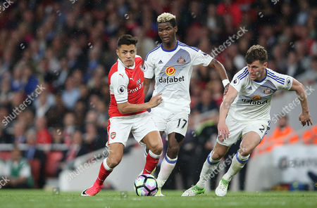 Alexis Sanchez Of Arsenal takes the ball past Didier Ndong Of Sunderland and Billy Jones Of Sunderland during the Premier League match between Arsenal and Sunderland on 16th May 2017 at The Emirates Stadium, London.