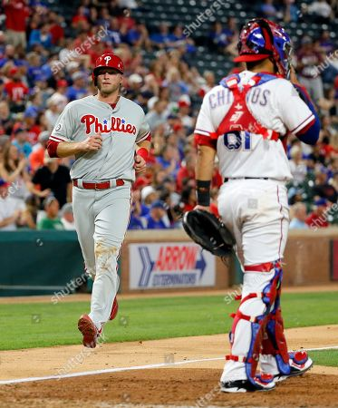 Michael Saunders, Robinson Chirinos Philadelphia Phillies' Michael Saunders, left, jogs home scoring on a Freddy Galvis single as Texas Rangers catcher Robinson Chirinos (61) stands by the plate in the seventh inning of a baseball game, in Arlington, Texas