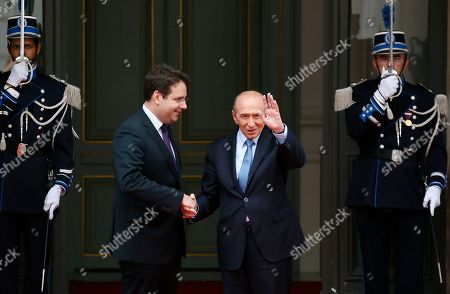 Newly named French Interior Minister Gerard Collomb, right, waves as he shakes hands with outgoing Interior Minister Matthias Fekl during the handover ceremony in Paris, Wednesday May, 17, 2017 in Paris. Collomb has been a prominent Socialist politician in France since becoming mayor of Lyon in 2001 _ France's third biggest city